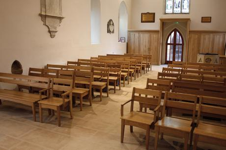 View along the nave with St Mary's chairs and benches and oak storage cupboards either side of the entrance
